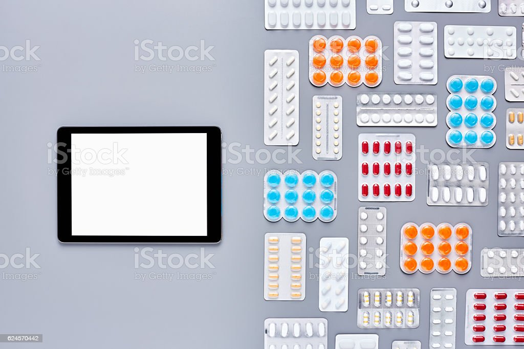 Flat lay of various blister backs arranged by digital tablet - foto de stock