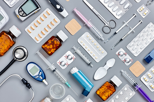 Flat lay of various medical supplies on gray background
