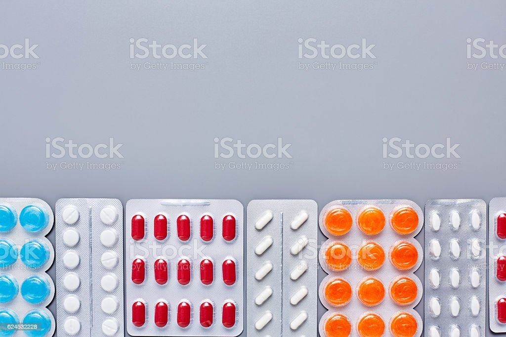 Flat lay of various medicines arranged on gray background stock photo