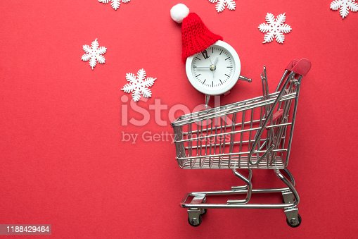 1136804881 istock photo Flat lay of winter holiday shopping made of shopping trolley , small clock with santa hat and white snowflakes isolated on red. 1188429464