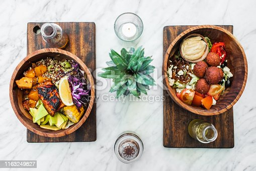 Flat lay of wooden bowls with fresh organic vegetarian food on white marble table. Falafel, hummus, avocado, vegetable salad, salmon steak. Olive oil on side. Healthy food concept.