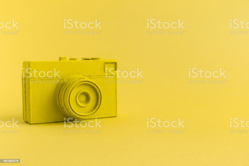 Flat lay of yellow colored retro camera surrealism abstract concept