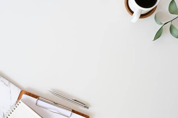 scrivania dell'ufficio laico piatta. spazio di lavoro con forniture per ufficio, matita, foglia verde con grafico di caffè e carta su tavolo da vista superiore bianco. - flat lay foto e immagini stock
