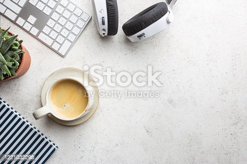 Flat lay or top view office table desk. Workspace with blank, keyboard, pen, green plant succulent, and coffee cup on white background.