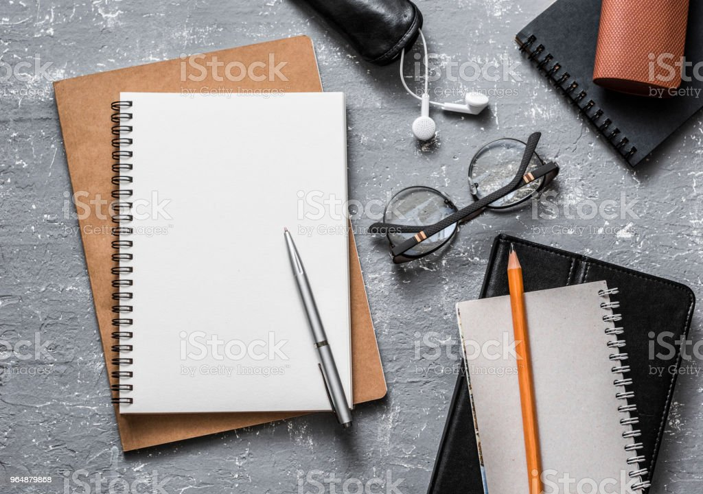 Flat lay office workplace. Business or education accessories - blank notepad glasses, pens, pencils, headphones on grey background, top view. Space for text royalty-free stock photo