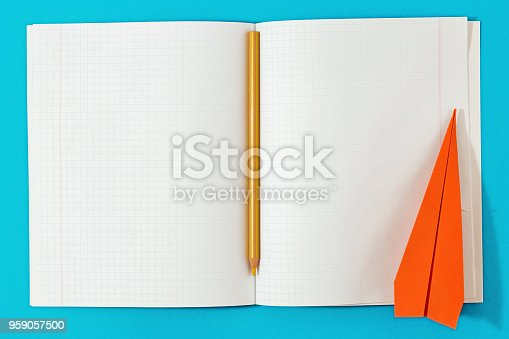 istock Flat lay open notebook with pencil and paper airplane on blue background. Top view minimalist education background 959057500