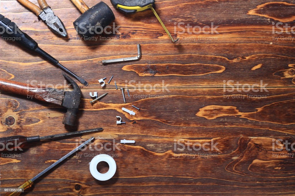 flat lay or top view dirty corrosive hammer, screwdriver, nail, fischer, seal, plier at dark wooden board stock photo