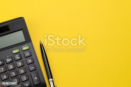 istock Flat lay or top view of black pen with calculator on vivid yellow background table with blank copy space, math, cost, tax or investment calculation 924620660