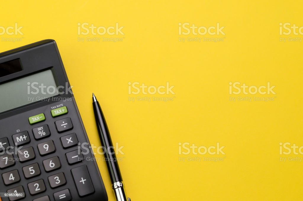 Flat lay or top view of black pen with calculator on vivid yellow background table with blank copy space, math, cost, tax or investment calculation stock photo