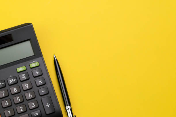 Flat lay or top view of black pen with calculator on vivid yellow background table with blank copy space, math, cost, tax or investment calculation - foto stock
