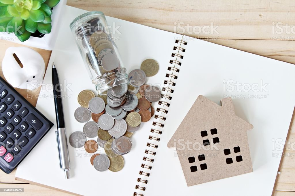 Flat lay or top view of wood house model and coins scattered from glass jar on open blank notebook paper royalty-free stock photo