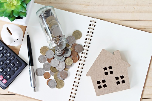 istock Flat lay or top view of wood house model and coins scattered from glass jar on open blank notebook paper 840393626