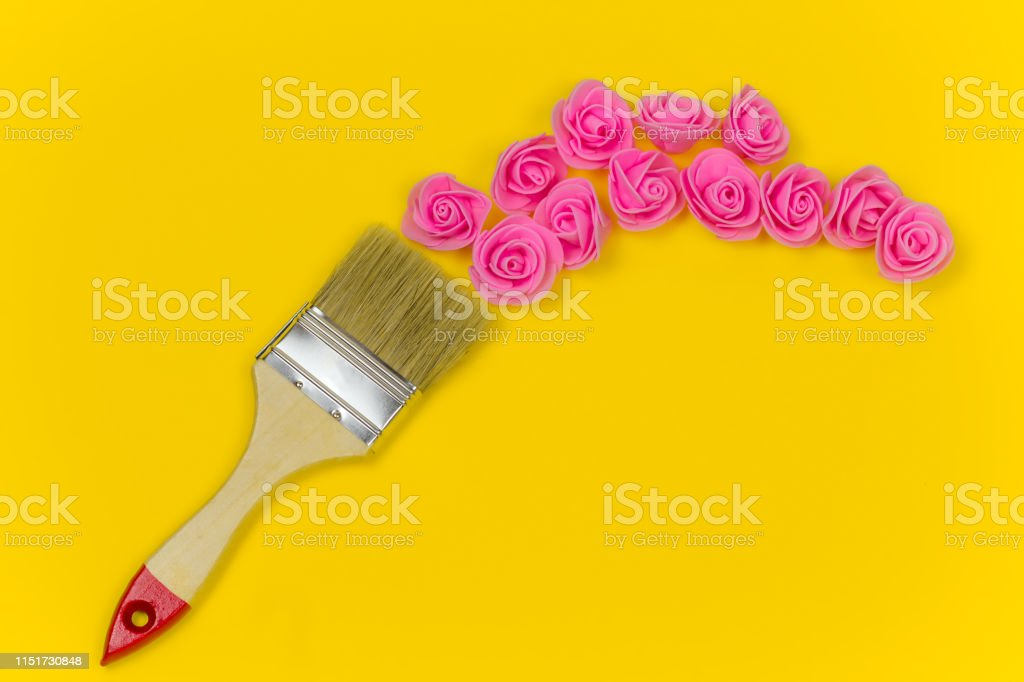 top view flat lay paint brush with bouquet of rose flowers on vibrant...