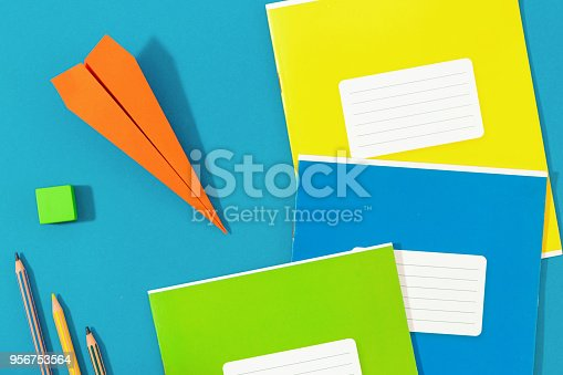istock Flat lay paper airplane with school supplies on blue background. Top view back to school concept 956753564