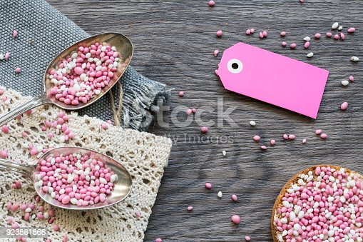 istock flat lay part birth scene with two vintage silver spoons with rusk, typical Dutch food muisjes, pink and white aniseed, for announcement a daughter, baby girl is born 923861866