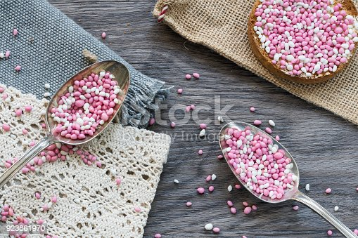 istock flat lay part birth scene with two vintage silver spoons with rusk, typical Dutch food muisjes, pink and white aniseed, for announcement a daughter, baby girl is born 923861970