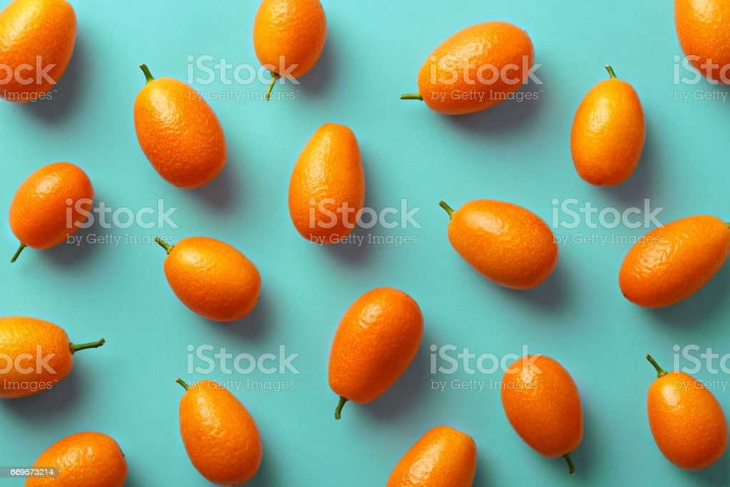 Flat lay pattern of fresh kumquats on a colorful background. Top view stock photo