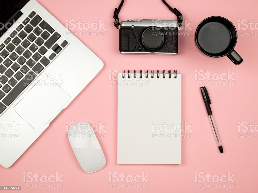 Flat lay photo of home office desk with laptop, notebook and camera. Colored background stock photo