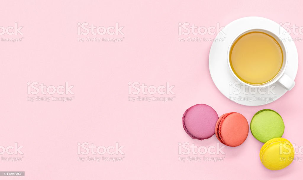 Flat lay photo of office desk with tea mug, macaroons on pink and...
