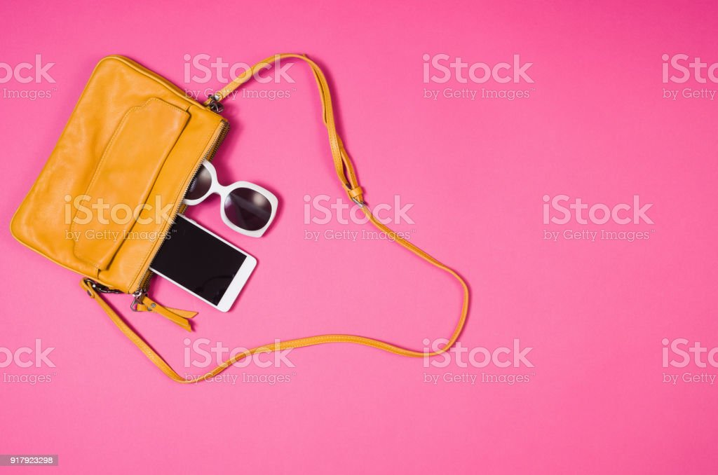 Woman\'s accessories lying flat on pink paper table background. Pastel...