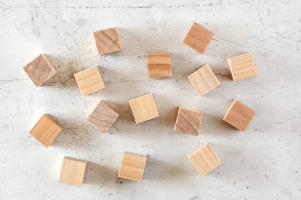 Flat lay photo - scattered plain wood cubes on white concrete like board. stock photo