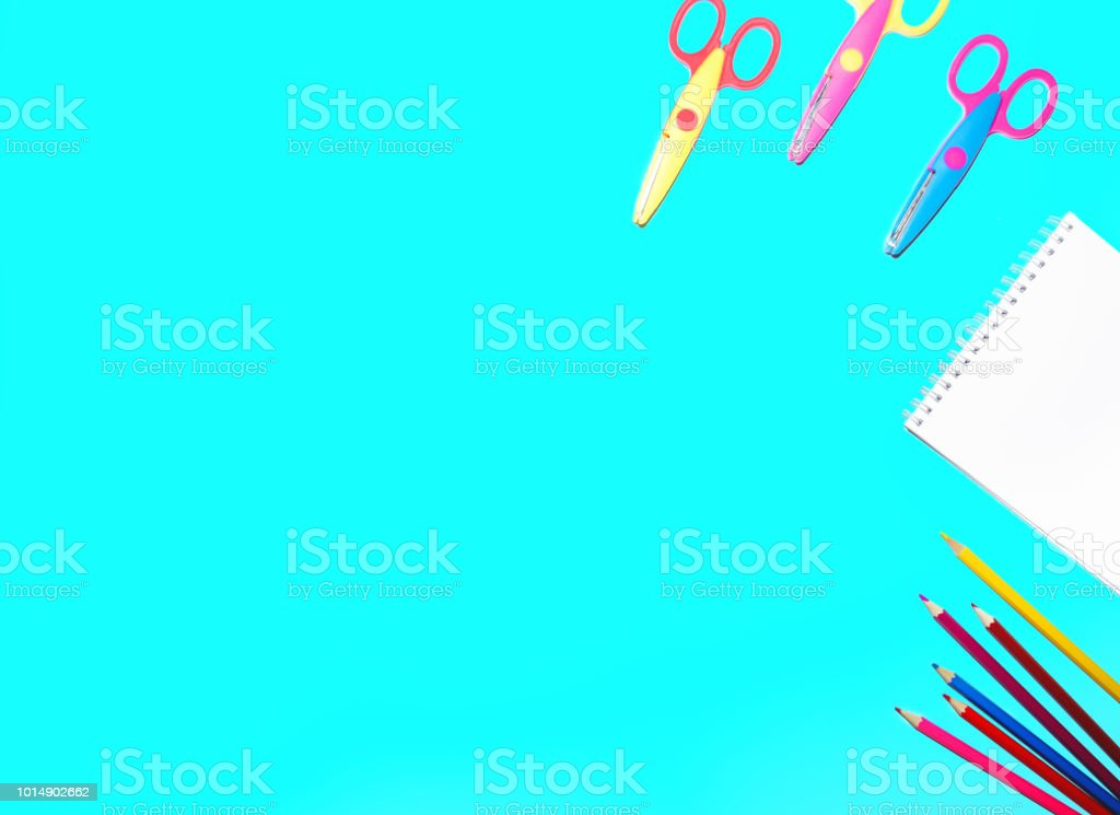 picture of colored pencils, notepad and scissors lined on a flat...