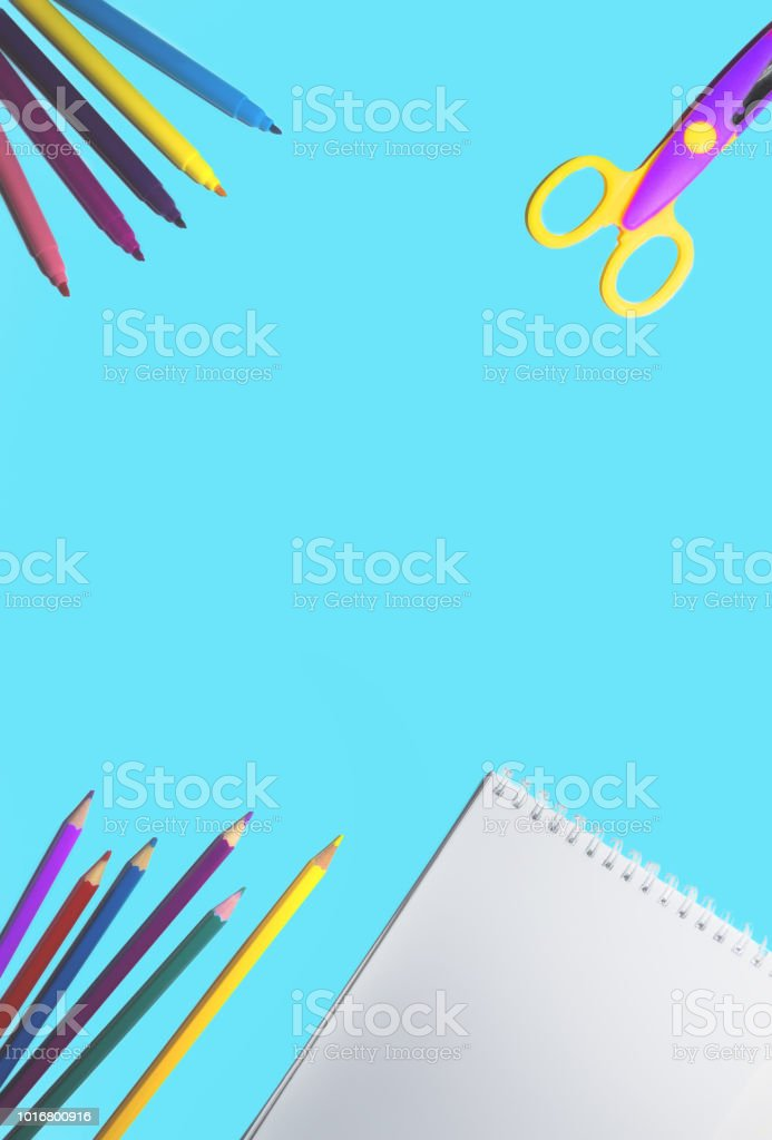 flat lay picture of colored pencils, notepad and scissors lined on a...