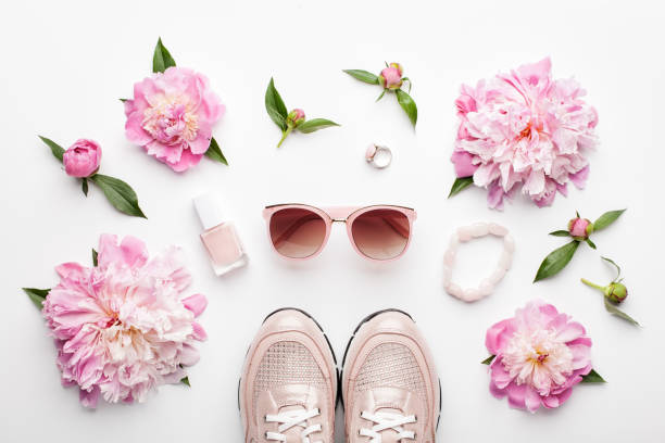 Flat lay pink feminine accessories and peony flowers on white. stock photo