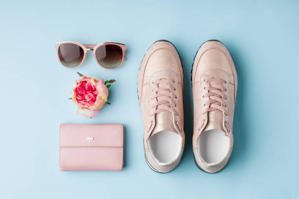 Flat lay pink feminine accessories on blue background. stock photo