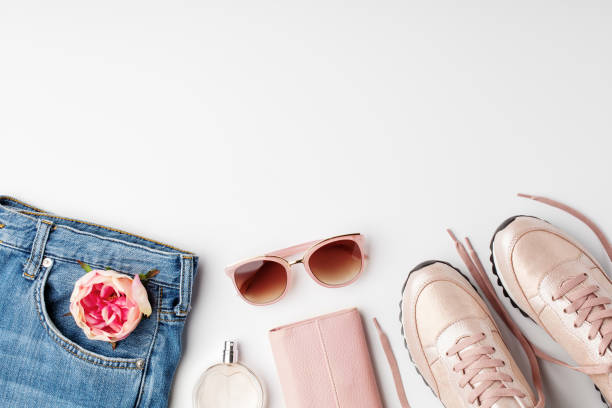 Flat lay pink feminine clothes and accessories on white background. stock photo