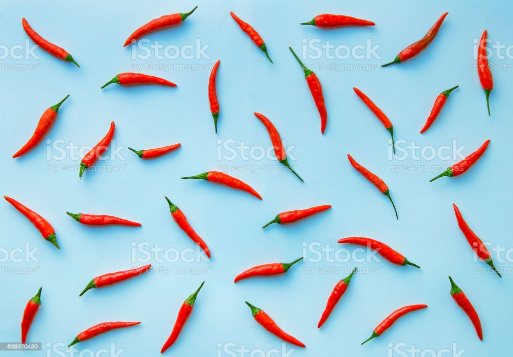 Flat lay red chili peppers pattern on blue background Flat lay red chili peppers pattern on blue background. Top view Cayenne Powder Stock Photo