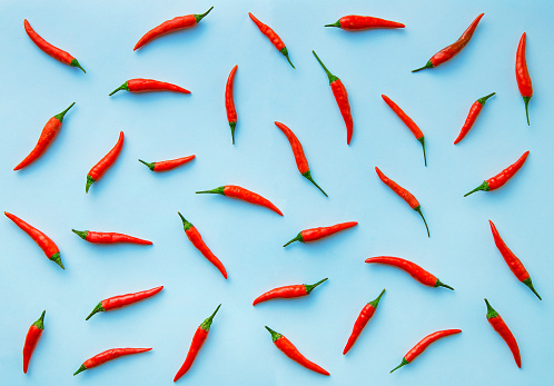 Flat Lay Red Chili Peppers Pattern On Blue Background Stock Photo - Download Image Now