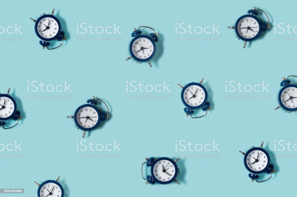 Flat lay retro beautiful new alarm clock on blue color background. Pattern. Top - Zbiór zdjęć royalty-free (Alarm)