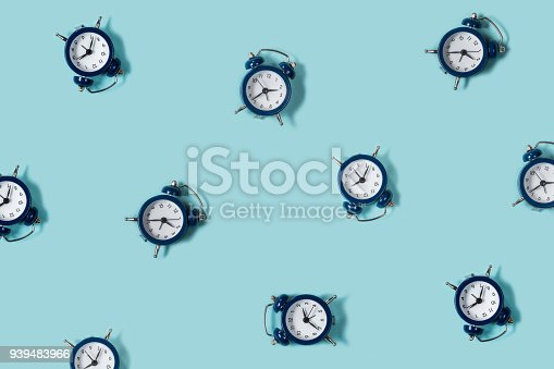 istock Flat lay retro beautiful new alarm clock on blue color background. Pattern. Top 939483966