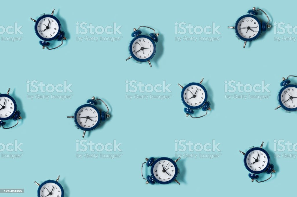 Flat lay retro beautiful new alarm clock on blue color background. Pattern. Top stock photo