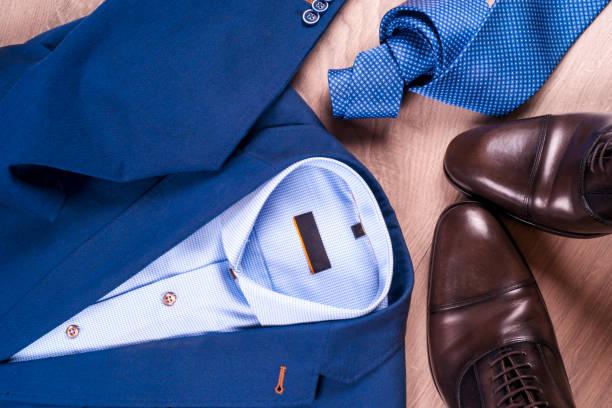 Plat poser ensemble de vêtements classique mens comme costume bleu, chemises, chaussures marron, ceinture et cravate sur fond en bois. - Photo