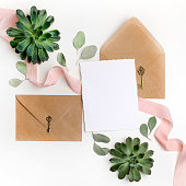 Flat lay shot of letter and eco paper envelope on white background. Wedding invitation cards or love letter with plant. Valentine's day or other holiday concept.