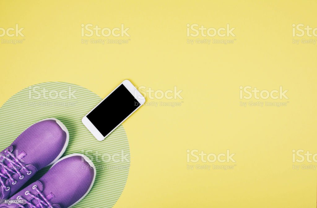 Flat lay shot of sneakers and smartphone on yellow background with copy space for your text. stock photo