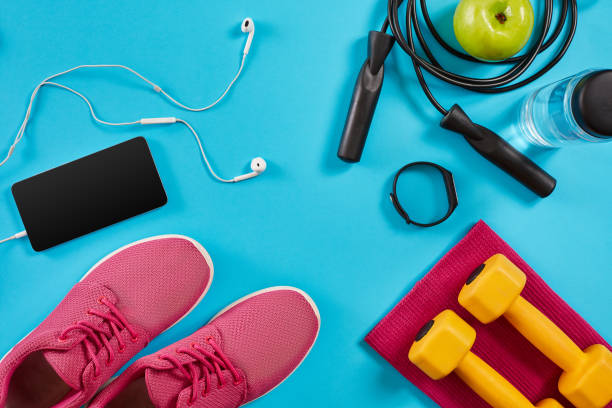 flat lay shot of sneakers, jumping rope, dumbbells and smartphone on blue background - тренажер стоковые фото и изображения