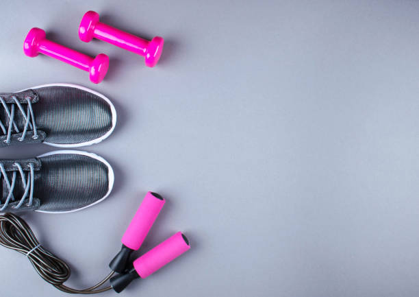 flat lay shot of sneakers, jumpung rope and dumbbells. - exercise equipment stock photos and pictures