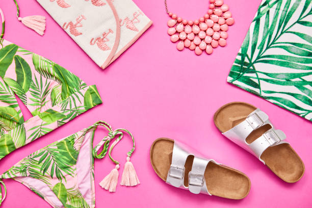 Flat lay shot of summer vacation accessories on pink background stock photo