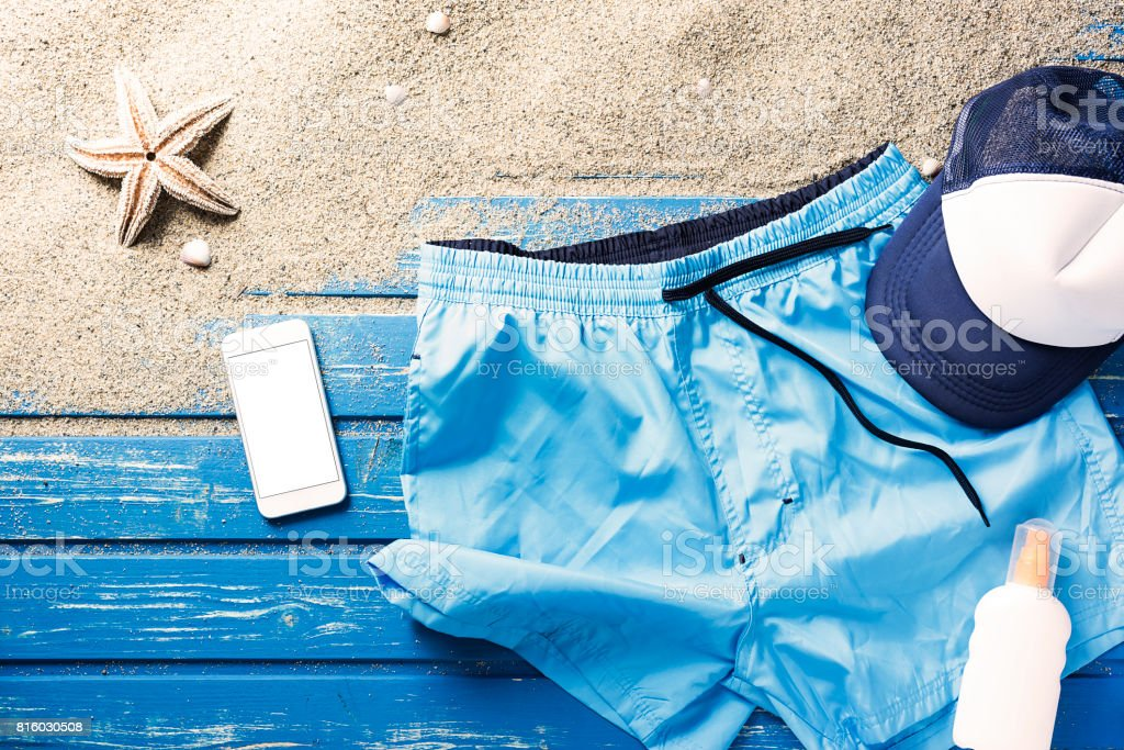 Flat lay shot, swim shorts and phone on blue beach platform stock photo