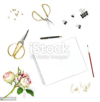Flat lay with sketchbook, watercolor brush, office tools, rose flowers on white background