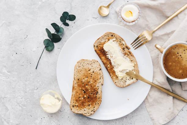 plana lay fatia de torrada com manteiga branca num prato. conceito de pequeno-almoço - torrada - fotografias e filmes do acervo
