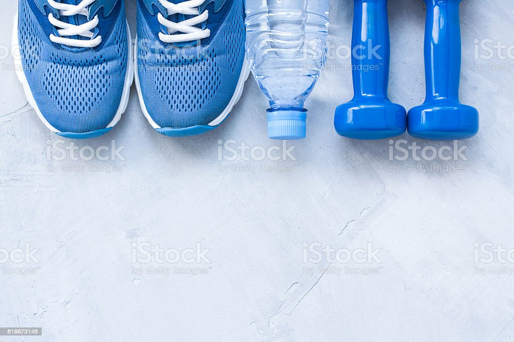 Flat lay sport shoes, bottle of water and dumbbells on gray concrete...