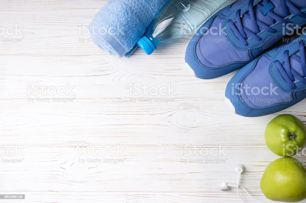 Flat lay sport shoes, bottle of water, apples, towel and earphones on white background. Sport equipment. Healthy lifestyle, sport and diet concept royalty-free stock photo