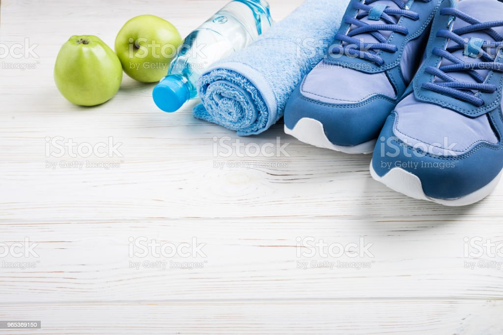 Flat lay sport shoes, bottle of water, apples, towel and earphones on white wooden background. Sport equipment. Healthy lifestyle, sport and diet concept zbiór zdjęć royalty-free