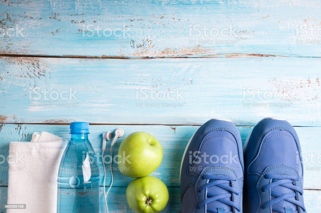 平躺運動鞋, 瓶水, 蘋果, 毛巾和耳機在白色背景。運動器材。健康的生活方式, 運動和飲食觀念。複製空間 - 免版稅一組物體圖庫照片