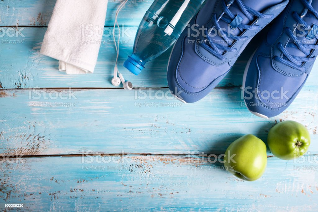 Flat lay sport shoes, bottle of water, apples, towel and earphones on blue background. Sport equipment. Healthy lifestyle, sport and diet concept. Copy space royalty-free stock photo