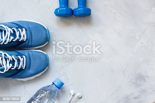 istock Flat lay sport shoes, bottle of water, dumbbells and earphones 609076630